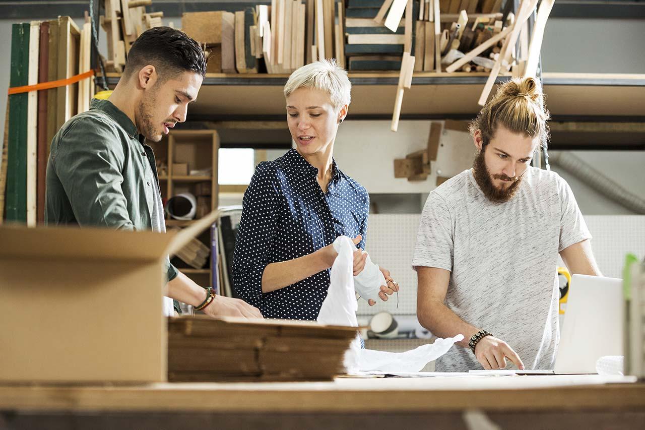 3 Menschen in einer Werkstadt umgeben von Kartons und Holz